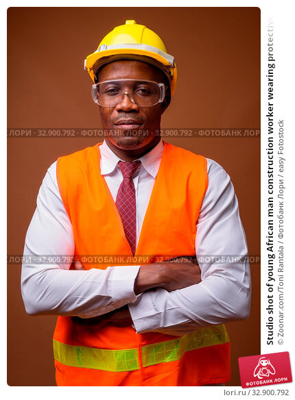 Studio shot of young African man construction worker wearing protective glasses against brown background. Стоковое фото, фотограф Zoonar.com/Toni Rantala / easy Fotostock / Фотобанк Лори