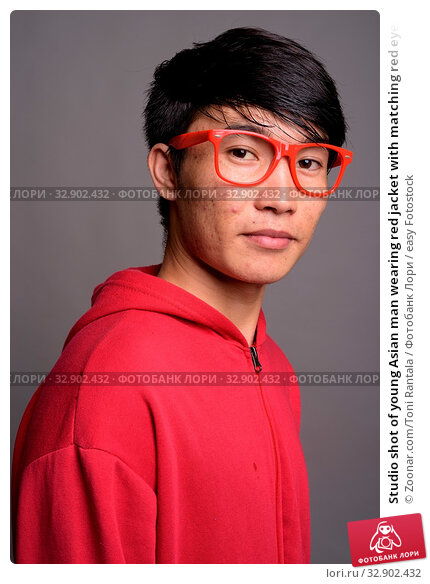 Studio shot of young Asian man wearing red jacket with matching red eyeglasses against gray background. Стоковое фото, фотограф Zoonar.com/Toni Rantala / easy Fotostock / Фотобанк Лори