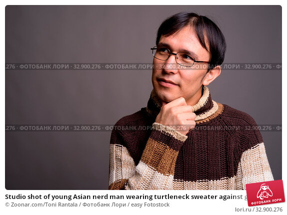 Studio shot of young Asian nerd man wearing turtleneck sweater against gray background. Стоковое фото, фотограф Zoonar.com/Toni Rantala / easy Fotostock / Фотобанк Лори