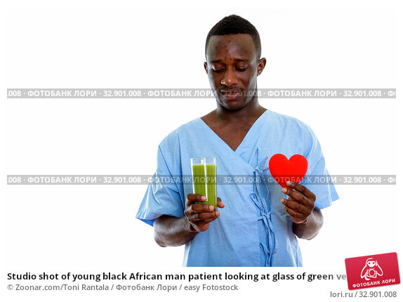 Studio shot of young black African man patient looking at glass of green vegetable smoothie and holding red heart. Стоковое фото, фотограф Zoonar.com/Toni Rantala / easy Fotostock / Фотобанк Лори