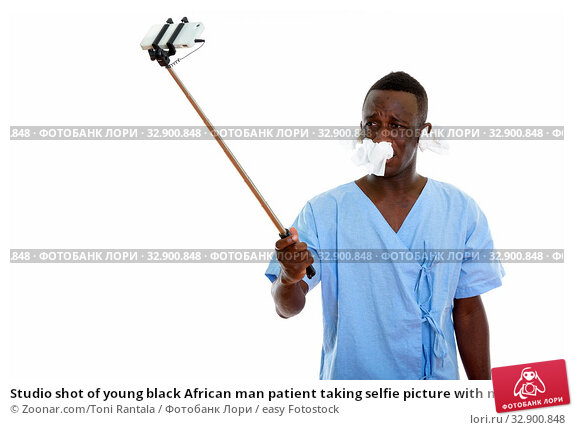Studio shot of young black African man patient taking selfie picture with mobile phone on selfie stick with tissues on his ears and nose. Стоковое фото, фотограф Zoonar.com/Toni Rantala / easy Fotostock / Фотобанк Лори