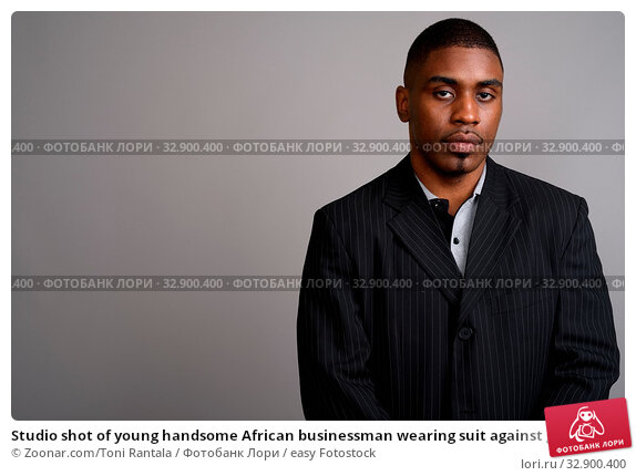Studio shot of young handsome African businessman wearing suit against gray background. Стоковое фото, фотограф Zoonar.com/Toni Rantala / easy Fotostock / Фотобанк Лори