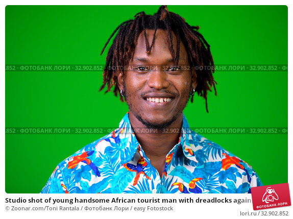 Studio shot of young handsome African tourist man with dreadlocks against chroma key with green background. Стоковое фото, фотограф Zoonar.com/Toni Rantala / easy Fotostock / Фотобанк Лори