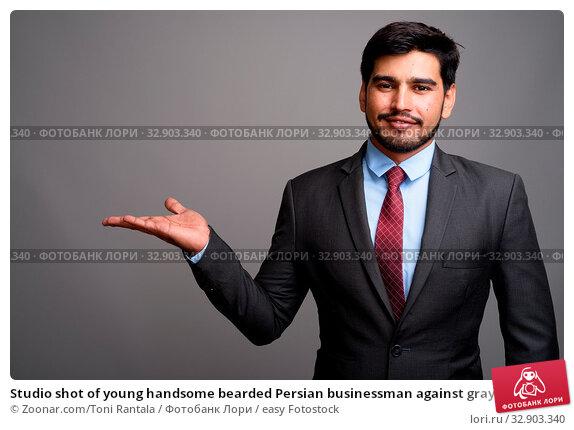 Studio shot of young handsome bearded Persian businessman against gray background. Стоковое фото, фотограф Zoonar.com/Toni Rantala / easy Fotostock / Фотобанк Лори