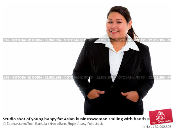 Studio shot of young happy fat Asian businesswoman smiling with hands on pockets. Стоковое фото, фотограф Zoonar.com/Toni Rantala / easy Fotostock / Фотобанк Лори