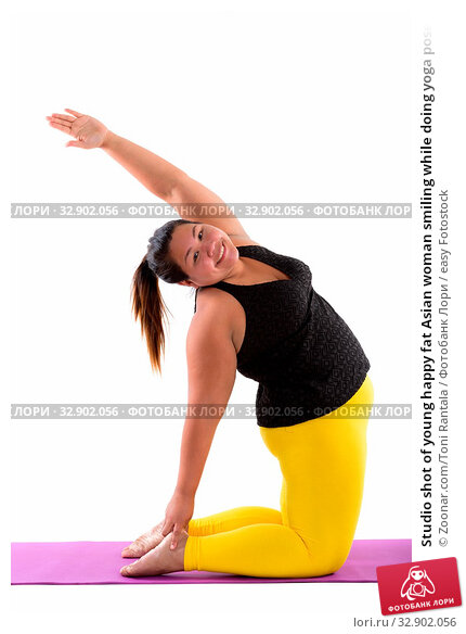 Studio shot of young happy fat Asian woman smiling while doing yoga poses. Стоковое фото, фотограф Zoonar.com/Toni Rantala / easy Fotostock / Фотобанк Лори