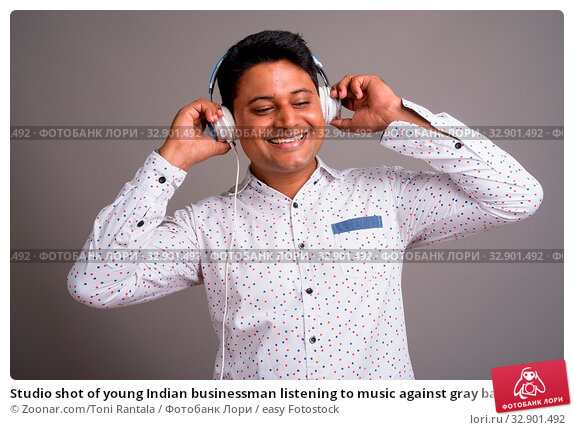 Studio shot of young Indian businessman listening to music against gray background. Стоковое фото, фотограф Zoonar.com/Toni Rantala / easy Fotostock / Фотобанк Лори