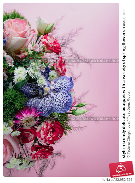 stylish trendy delicate bouquet with a variety of spring flowers, roses, orchids in a round box on a pink background. Copy space. Стоковое фото, фотограф Tetiana Chugunova / Фотобанк Лори