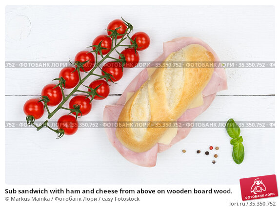 Sub sandwich with ham and cheese from above on wooden board wood. Стоковое фото, фотограф Markus Mainka / easy Fotostock / Фотобанк Лори