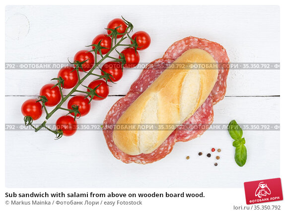 Sub sandwich with salami from above on wooden board wood. Стоковое фото, фотограф Markus Mainka / easy Fotostock / Фотобанк Лори