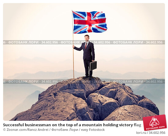 Successful businessman on the top of a mountain holding victory flag. Стоковое фото, фотограф Zoonar.com/Rancz Andrei / easy Fotostock / Фотобанк Лори
