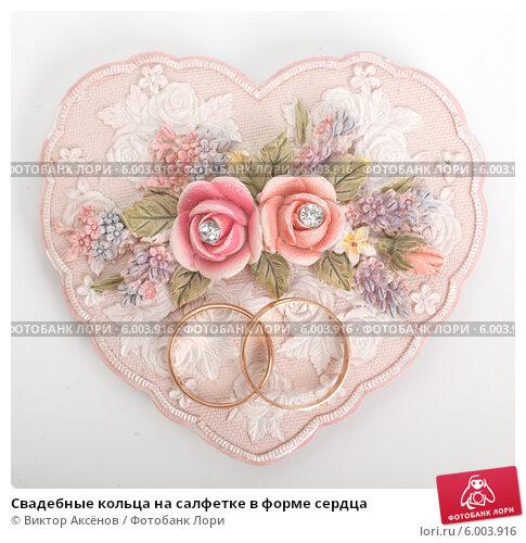 Купить «Свадебные кольца на салфетке в форме сердца», фото № 6003916, снято 13 июня 2014 г. (c) Виктор Аксёнов / Фотобанк Лори