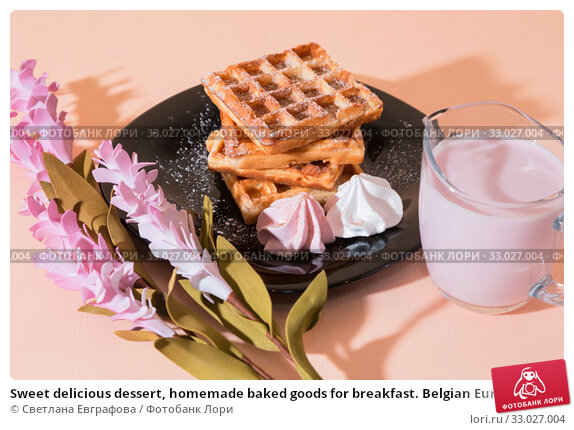 Sweet delicious dessert, homemade baked goods for breakfast. Belgian European soft waffles on a black plate, meringue, fruit berry yogurt. Стоковое фото, фотограф Светлана Евграфова / Фотобанк Лори