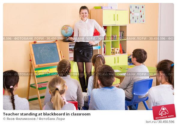 Teacher standing at blackboard in classroom. Стоковое фото, фотограф Яков Филимонов / Фотобанк Лори