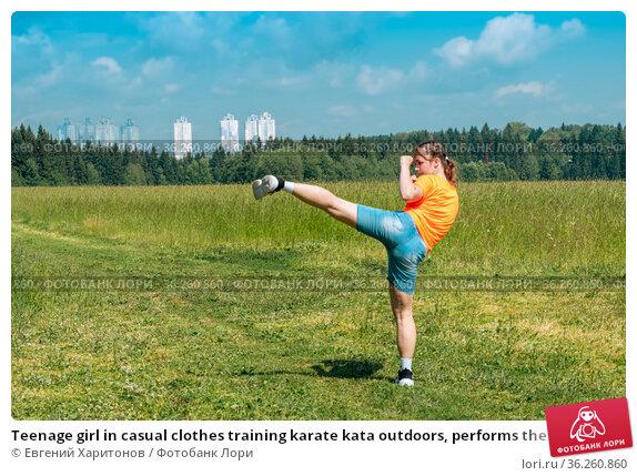 Teenage girl in casual clothes training karate kata outdoors, performs the uro mawashi geri (hook kick) Стоковое фото, фотограф Евгений Харитонов / Фотобанк Лори