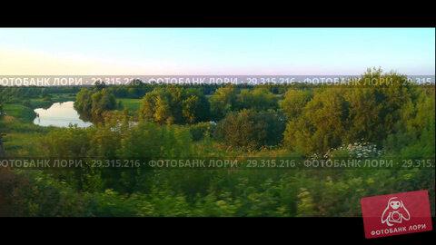 Купить «The beauty of the green spaces of Russia with a pond from the window of a moving train», видеоролик № 29315216, снято 20 июля 2018 г. (c) Элина Гаревская / Фотобанк Лори