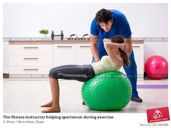 Купить «The fitness instructor helping sportsman during exercise», фото № 29138684, снято 10 июля 2018 г. (c) Elnur / Фотобанк Лори