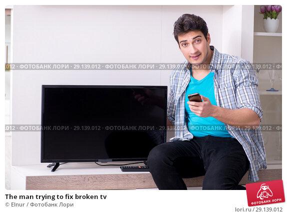 Купить «The man trying to fix broken tv», фото № 29139012, снято 9 марта 2018 г. (c) Elnur / Фотобанк Лори