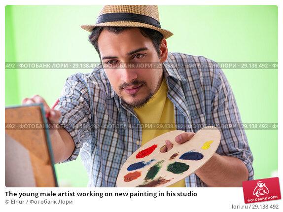 Купить «The young male artist working on new painting in his studio», фото № 29138492, снято 10 мая 2018 г. (c) Elnur / Фотобанк Лори