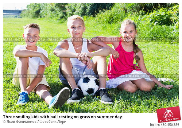 Three smiling kids with ball resting on grass on summer day. Стоковое фото, фотограф Яков Филимонов / Фотобанк Лори