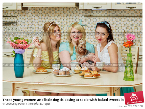Купить «Three young women and little dog sit posing at table with baked sweets in kitchen», фото № 28172168, снято 19 января 2016 г. (c) Losevsky Pavel / Фотобанк Лори