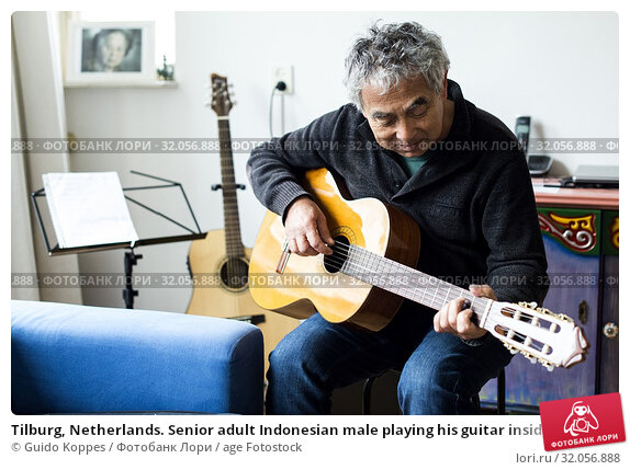 Tilburg, Netherlands. Senior adult Indonesian male playing his guitar inside his residential living room to prepare for a private, domestic concert. Стоковое фото, фотограф Guido Koppes / age Fotostock / Фотобанк Лори