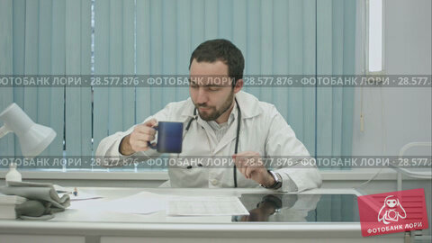 Купить «tired from work, bearded doctor drink from cup and continue woking with documents and x-rays», видеоролик № 28577876, снято 24 ноября 2015 г. (c) Vasily Alexandrovich Gronskiy / Фотобанк Лори