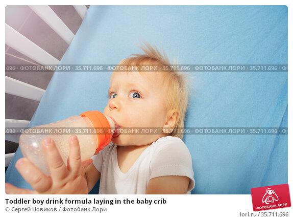Toddler boy drink formula laying in the baby crib. Стоковое фото, фотограф Сергей Новиков / Фотобанк Лори