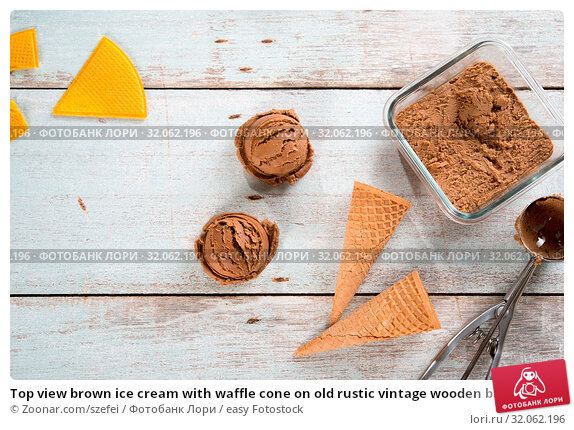 Top view brown ice cream with waffle cone on old rustic vintage wooden background. Стоковое фото, фотограф Zoonar.com/szefei / easy Fotostock / Фотобанк Лори