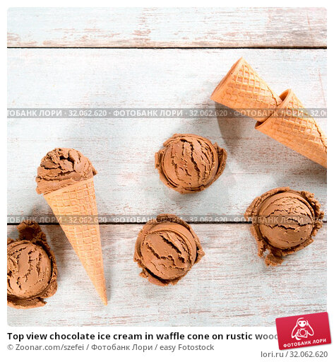 Top view chocolate ice cream in waffle cone on rustic wooden background. Copy space on above. Стоковое фото, фотограф Zoonar.com/szefei / easy Fotostock / Фотобанк Лори