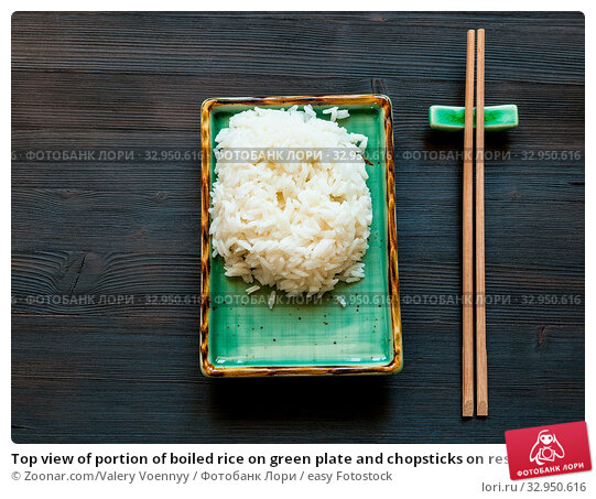 Top view of portion of boiled rice on green plate and chopsticks on rest on brown table with copyspace. Стоковое фото, фотограф Zoonar.com/Valery Voennyy / easy Fotostock / Фотобанк Лори
