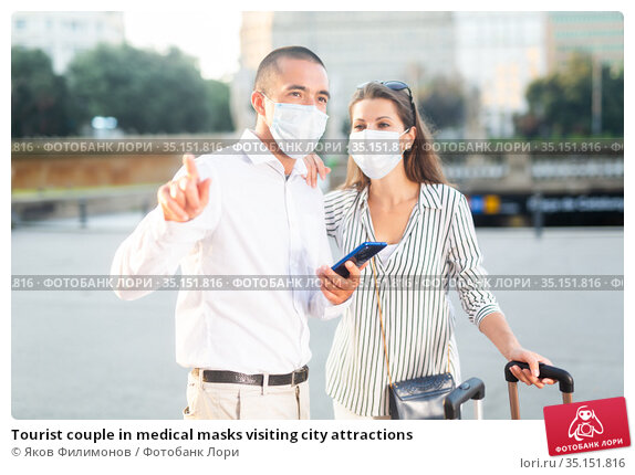 Tourist couple in medical masks visiting city attractions. Стоковое фото, фотограф Яков Филимонов / Фотобанк Лори