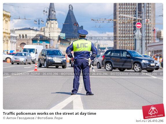Купить «Traffic policeman works on the street at day time», фото № 26410296, снято 18 октября 2018 г. (c) Антон Гвоздиков / Фотобанк Лори