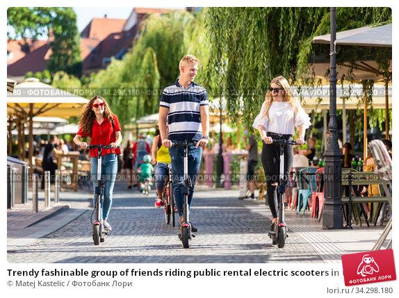 Trendy fashinable group of friends riding public rental electric scooters in urban city environment. New eco-friendly modern public city transport in Ljubljana, Slovenia. Стоковое фото, фотограф Matej Kastelic / Фотобанк Лори