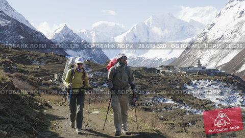 Купить «Two backpackers on the trekking Larke Pass in Nepal. Manaslu area.», видеоролик № 28688320, снято 18 июня 2018 г. (c) Dzmitry Astapkovich / Фотобанк Лори