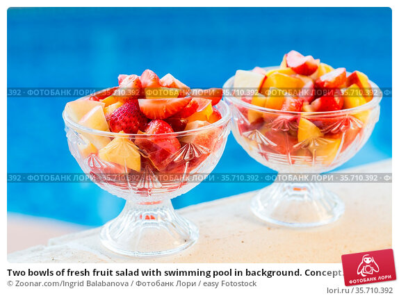 Two bowls of fresh fruit salad with swimming pool in background. Concept... Стоковое фото, фотограф Zoonar.com/Ingrid Balabanova / easy Fotostock / Фотобанк Лори