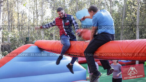Two cheerful men having funny battle by big boxing gloves on inflatable arena at amusement park. Стоковое видео, видеограф Яков Филимонов / Фотобанк Лори