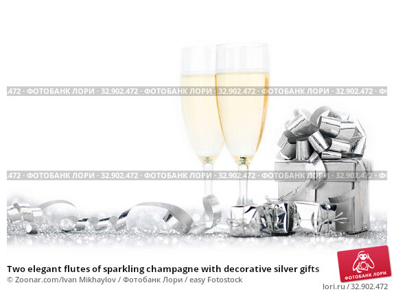 Two elegant flutes of sparkling champagne with decorative silver gifts. Стоковое фото, фотограф Zoonar.com/Ivan Mikhaylov / easy Fotostock / Фотобанк Лори