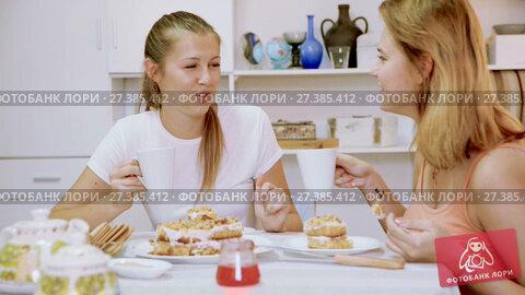 Купить «Two girlfriends are talking with tea and cake at home.», видеоролик № 27385412, снято 17 октября 2017 г. (c) Яков Филимонов / Фотобанк Лори