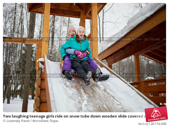 Купить «Two laughing teenage girls ride on snow tube down wooden slide covered with snow on winter day», фото № 28116040, снято 4 февраля 2017 г. (c) Losevsky Pavel / Фотобанк Лори
