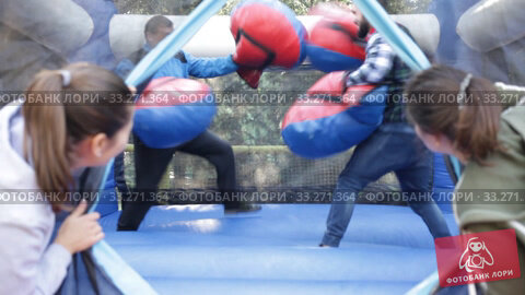 Two men in big boxing gloves boxing on inflatable ring in outdoor amusement park. Стоковое видео, видеограф Яков Филимонов / Фотобанк Лори