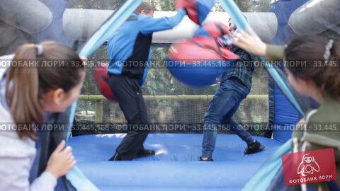 Two men in big boxing gloves boxing on inflatable ring in outdoor amusement park. Стоковое видео, видеограф Яков Филимонов / Фотобанк Лори