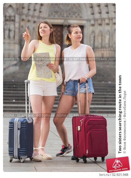 Купить «Two sisters searching route in the town», фото № 32921948, снято 29 мая 2017 г. (c) Яков Филимонов / Фотобанк Лори