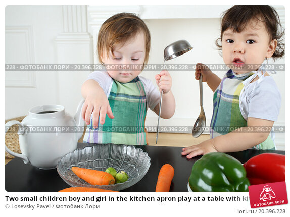 Купить «Two small children boy and girl in the kitchen apron play at a table with kitchenware and vegetables», фото № 20396228, снято 1 апреля 2014 г. (c) Losevsky Pavel / Фотобанк Лори