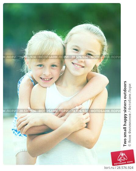 Купить «Two small happy sisters outdoors», фото № 28576924, снято 20 июля 2017 г. (c) Яков Филимонов / Фотобанк Лори