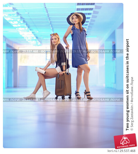 Купить «Two young women sit on suitcases in the airport», фото № 29537468, снято 20 июля 2018 г. (c) Serg Zastavkin / Фотобанк Лори