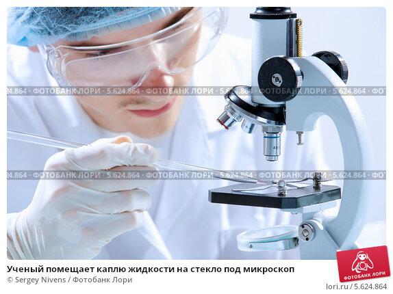 Ученый помещает каплю жидкости на стекло под микроскоп. Стоковое фото, фотограф Sergey Nivens / Фотобанк Лори