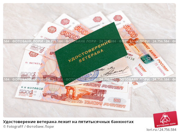 Купить «Удостоверение ветерана лежит на пятитысячных банкнотах», фото № 24756584, снято 18 апреля 2019 г. (c) FotograFF / Фотобанк Лори