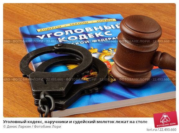 Купить «Уголовный кодекс, наручники и судейский молоток лежат на столе», фото № 22493660, снято 5 ноября 2015 г. (c) Денис Ларкин / Фотобанк Лори