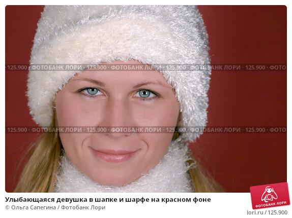 Улыбающаяся девушка в шапке и шарфе на красном фоне, фото № 125900, снято 27 сентября 2007 г. (c) Ольга Сапегина / Фотобанк Лори